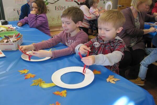 boy making a leaf wreath craft