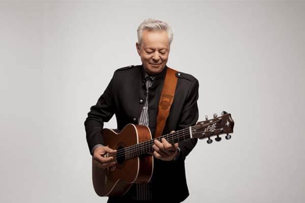 Tommy Emmanuel holding a guitar