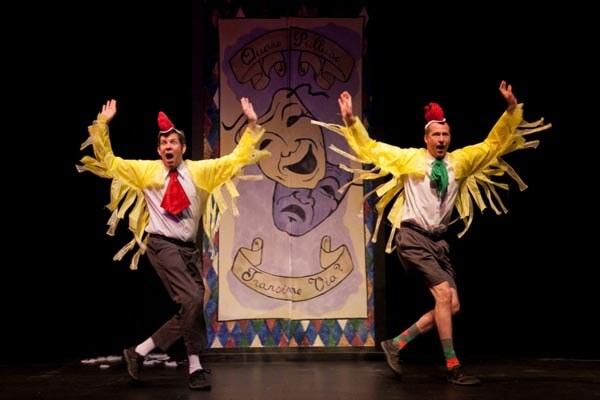 Two men wearing chicken costumes on stage in front of a poster depicting the comedy/tragedy theater masks.