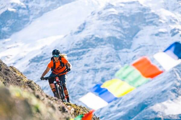 Mountain biker traversing rocky slop with prayer flags in foreground