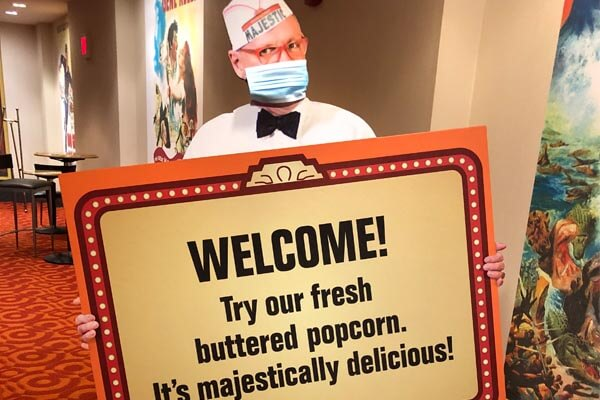 Standee of concessions seller holding sign that says